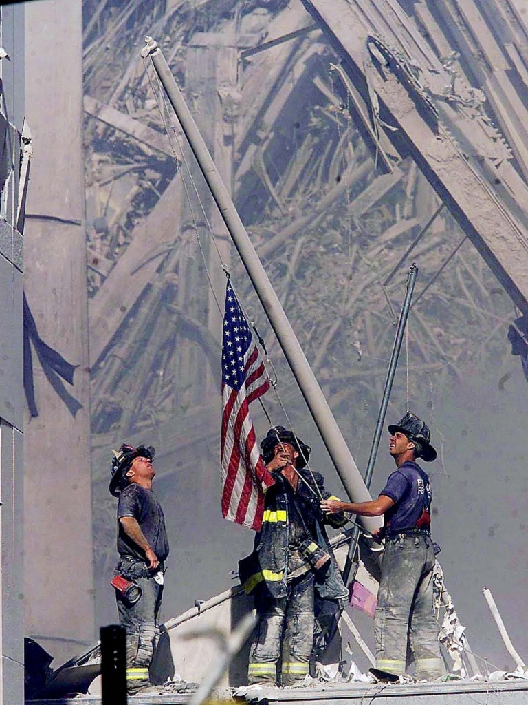 911 fire fighters hoisting flag